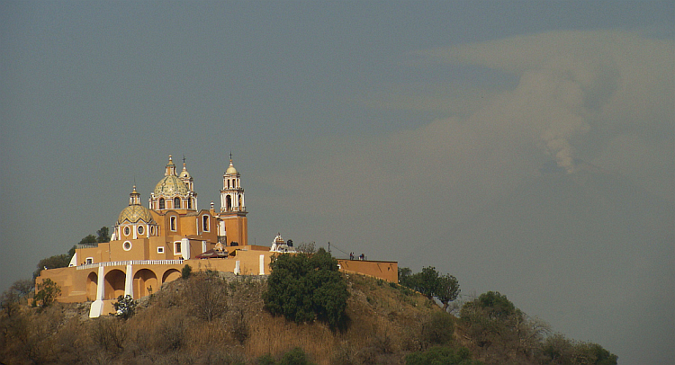 Church of Cholula with the volcano Popocatépetl veiled in ash clouds